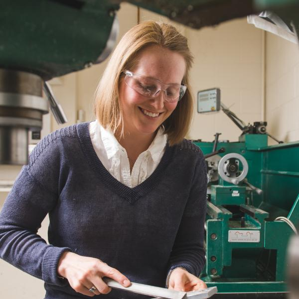 Madie Kern using the lathe in the lab to device fabrication