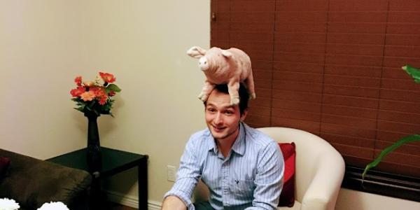 A man sitting down with a pig doll on his head