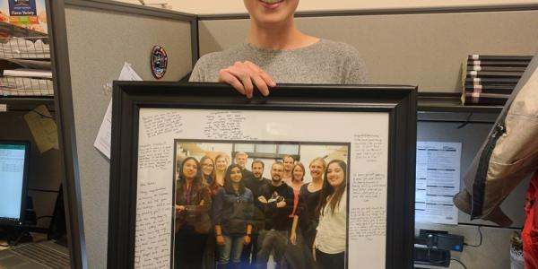 Keesha with a group picture in a frame with a lot of messages