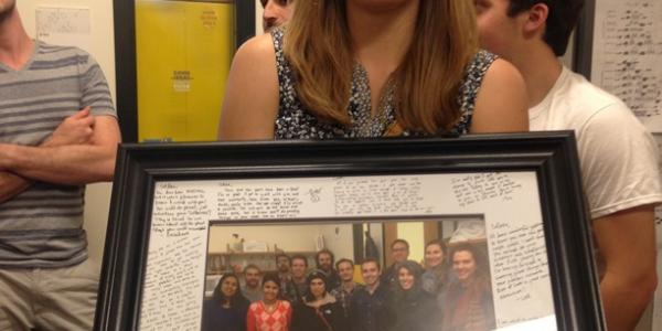 Colleen holding a team picture frame with a lot of messages