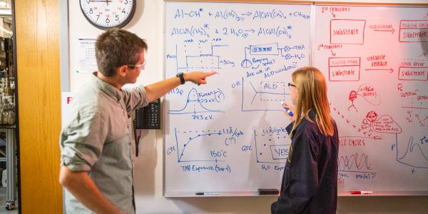 Jessica Murdzek & Austin Cano on the Whiteboard in the Laboratory; University of Colorado at Boulder, Steven M. George Research Group