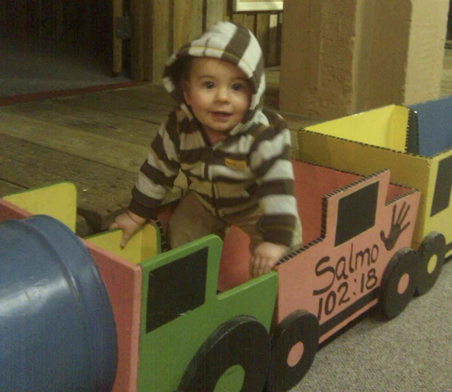 little boy playing in cardboard train
