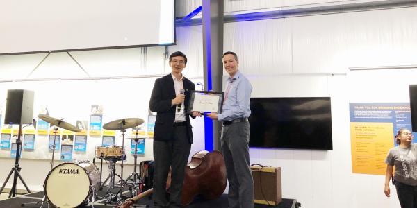 Greg and Yiguang holding up an award