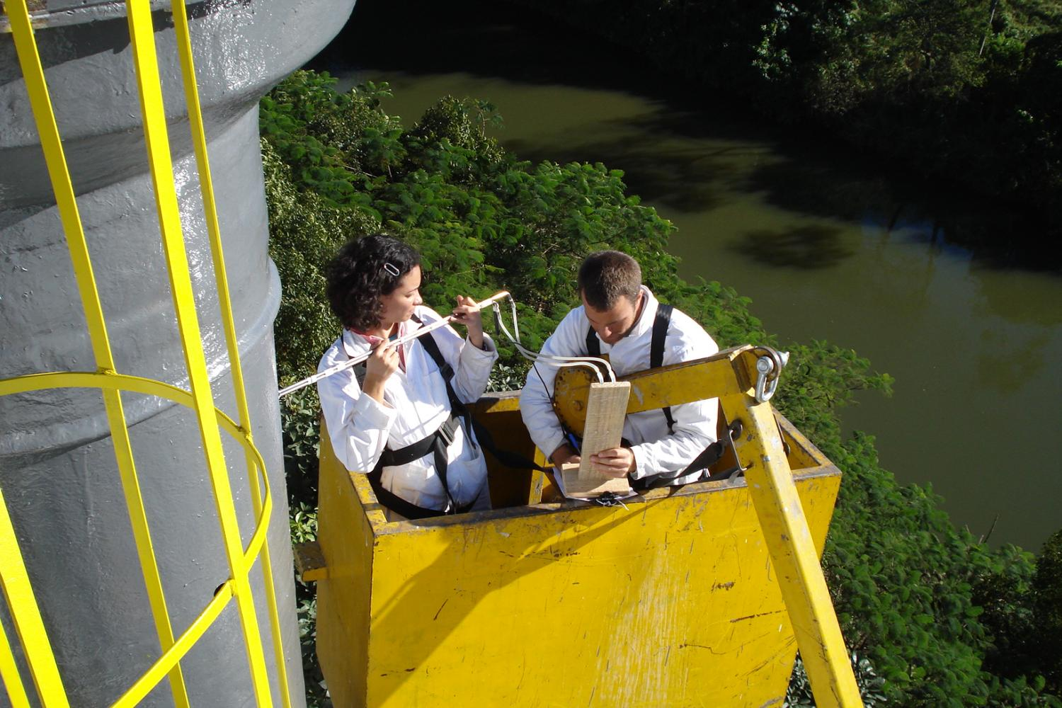 Dr. Vance in the bucket of a crane measuring the flow rate of a 120-ft smokestack.