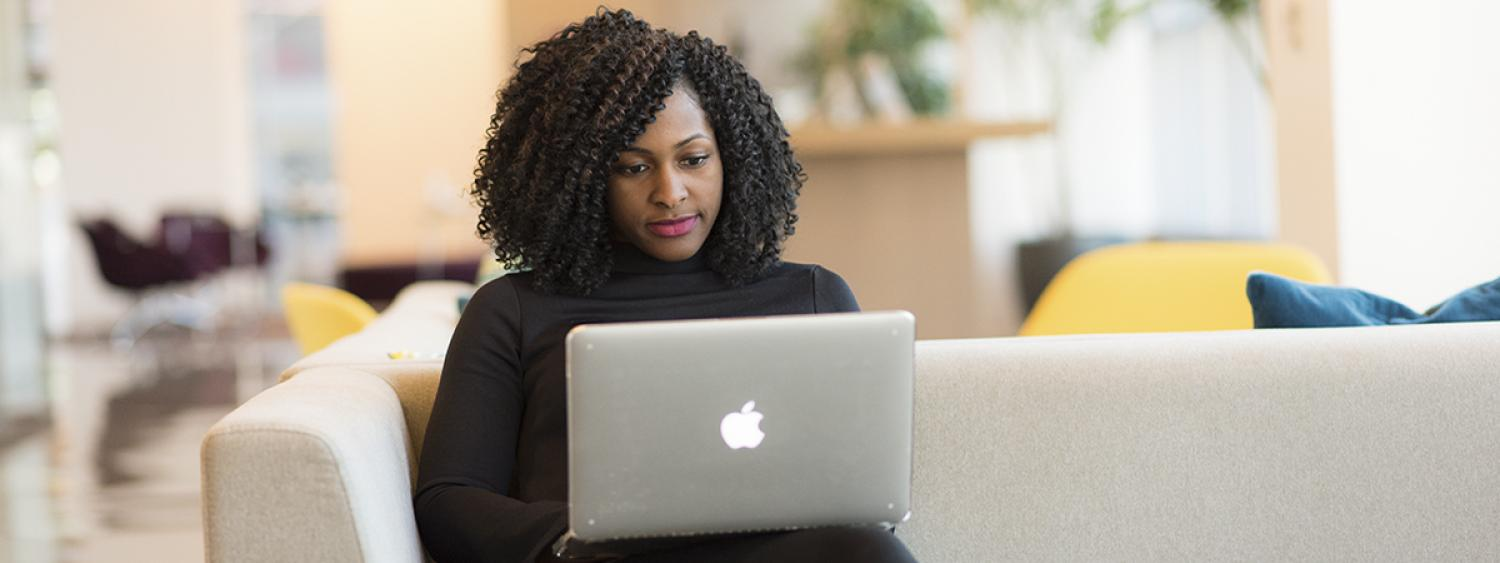 African American woman typing on a computer in office lounge setting