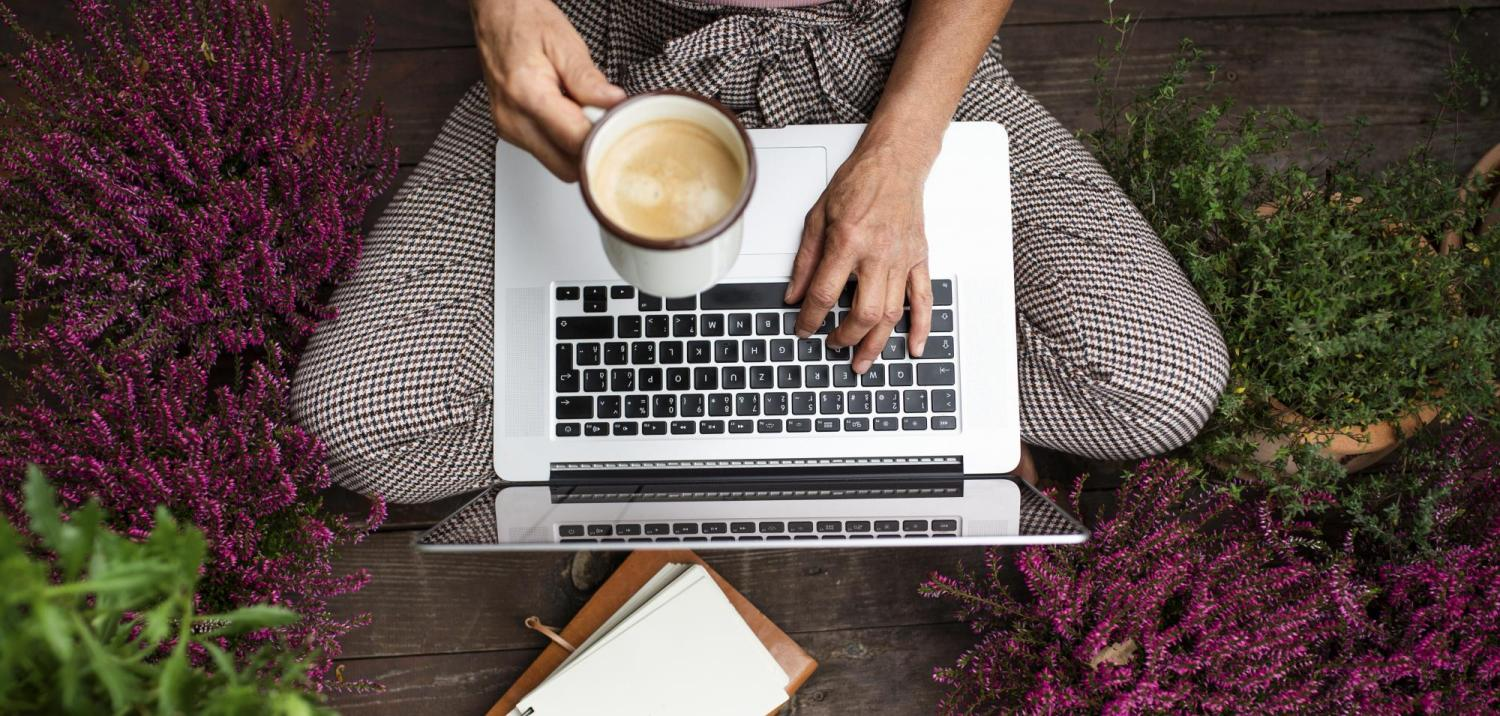 Lower body of a woman with laptop on her lap and coffee in her hand