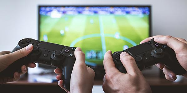 2 people holding a video game controller each with a soccer game in the background on a tv
