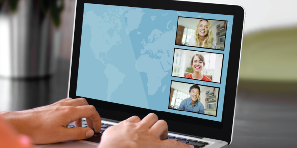 Woman typing and video conferencing on computer with three people
