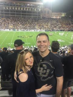 John and Sarah cheering on the Buffs at their 10-year law school reunion.