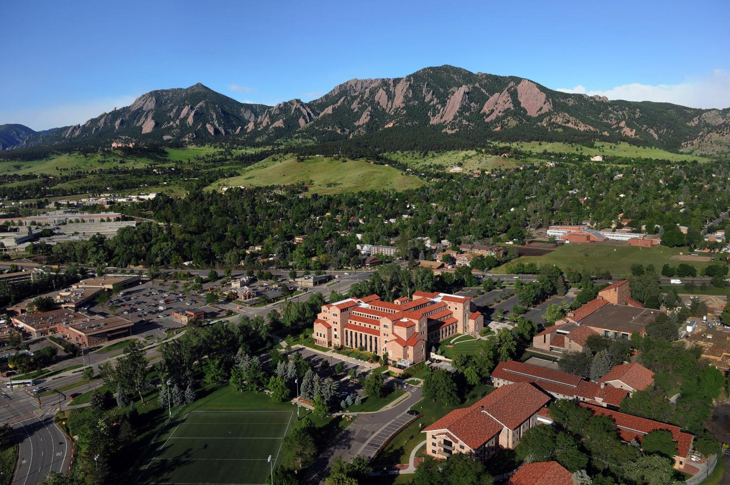 Aerial shot of the law school building with the Flatirons in the background