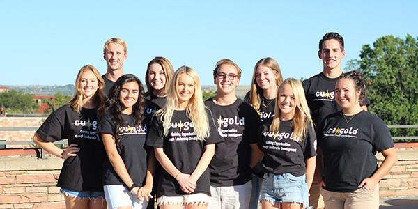 Students posing in CU Gold T-shirts