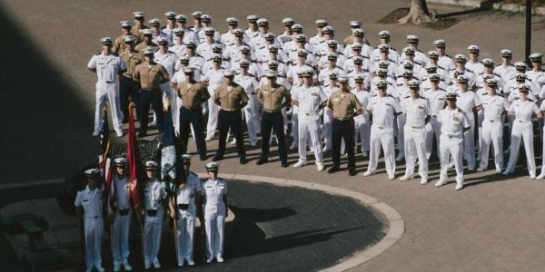 Navy ROTC standing at attention before an American flag