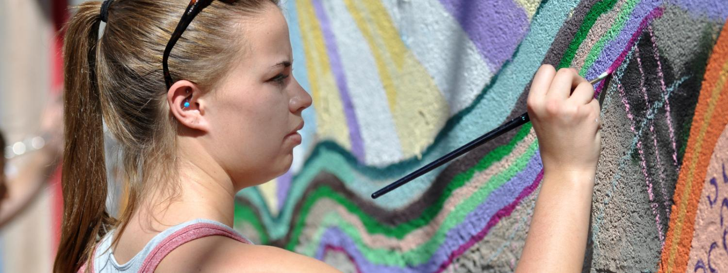 female student painting on a pastel wavy mural