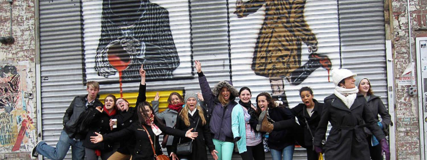 a bunch of students jumping up and laughing in front of a NYC mural