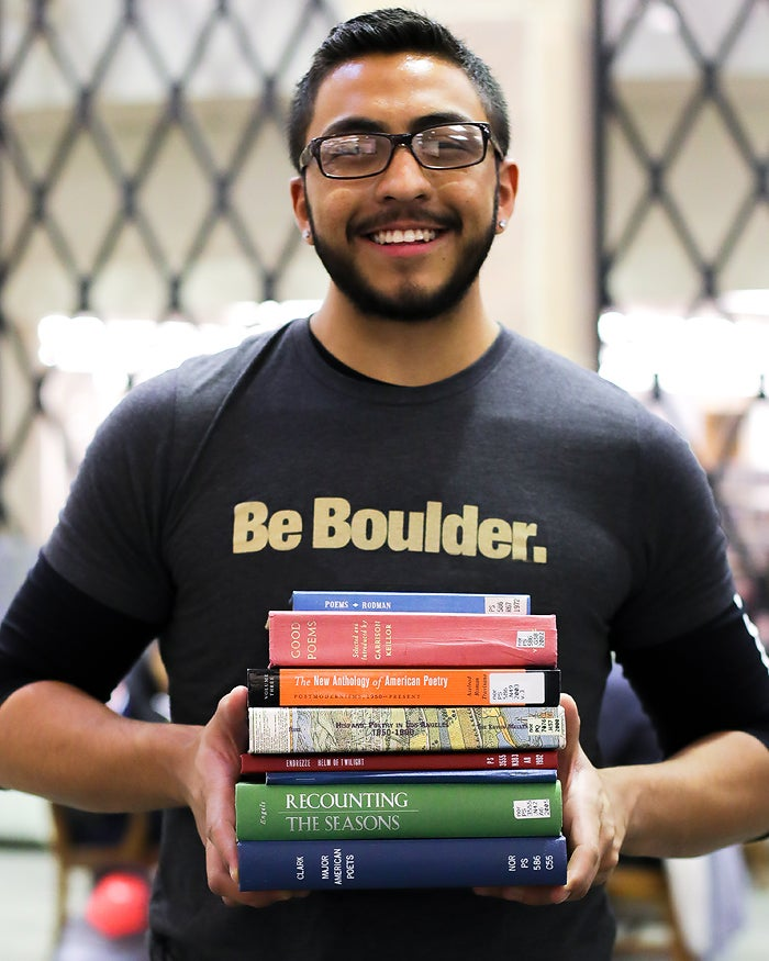 Student holding a stack of poetry books
