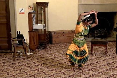 Student performing Bharatnayam in traditional dress.