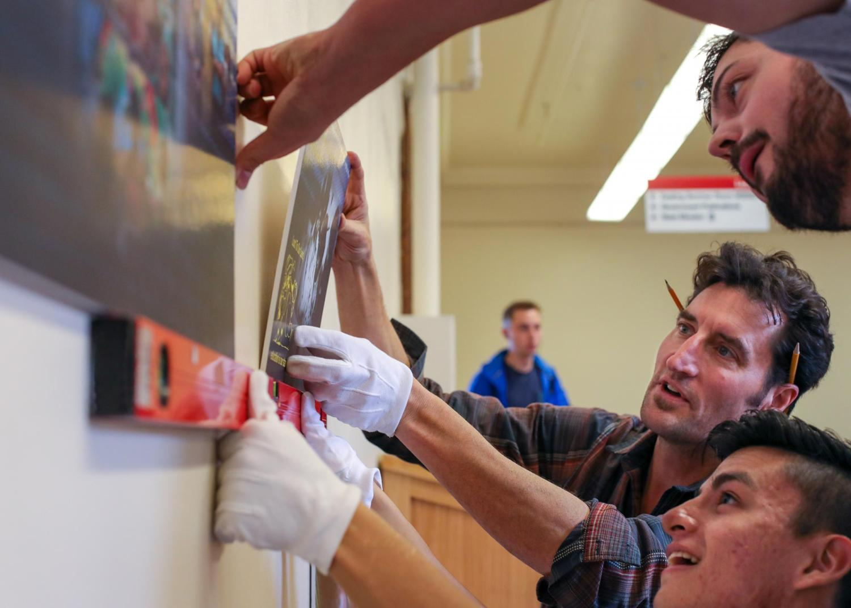 Students helping hang the UMAS exhibit