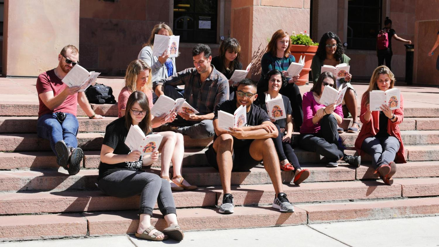 A group sits on the steps of Norlin reading Sabrina & Corina