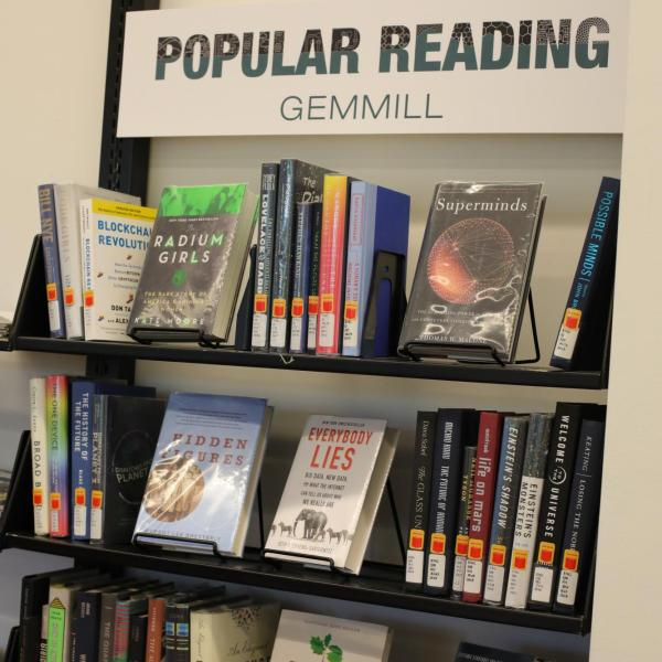 bookshelf with sign Popular Reading Gemmill at the top, holding four shelves of books with colorful colors