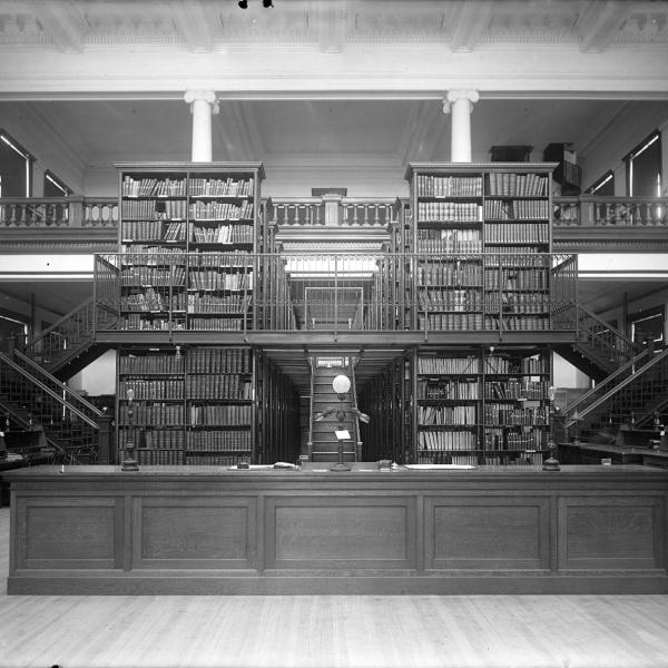 Black and white image of the old CU Boulder Library showing a desk with structural book stack shelves and stairs behind