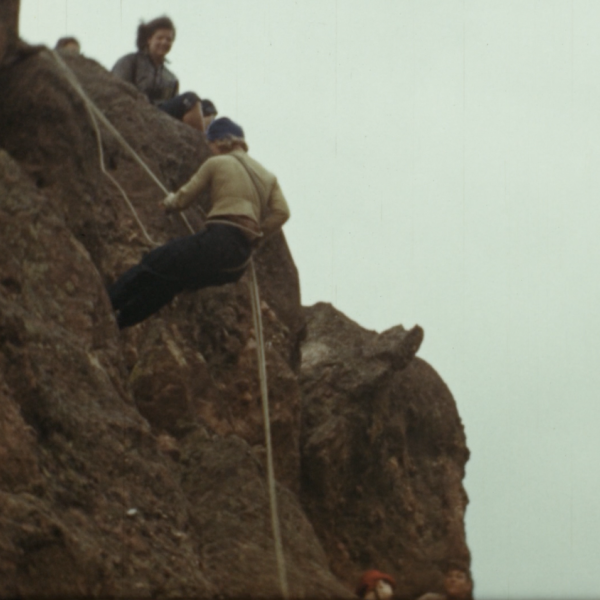 Man rappeling down a cliff as people look on