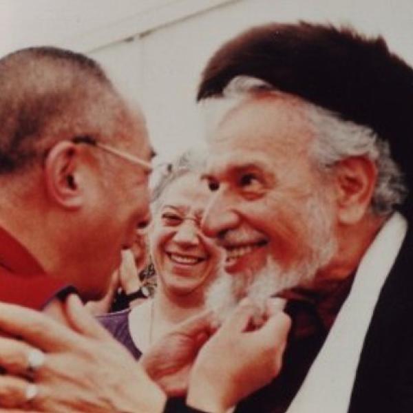Man in traditional Jewish garb embracing the Dalai Lama