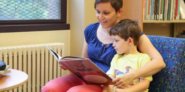 Faculty member Stephanie Bonjack reads to her young son in the CYAC section of Norlin.