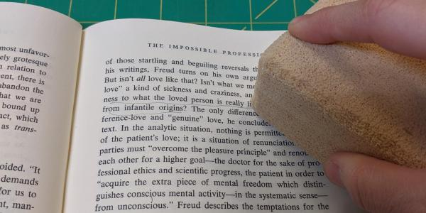 Erasing marginalia from a book with a chemical sponge.