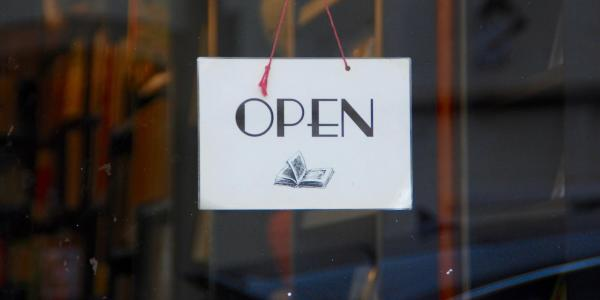 An open sign with a book on it that is in a window of a shop.
