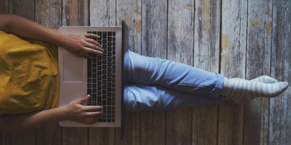 Image of someone's legs, sitting on hardwood floor with laptop on lap