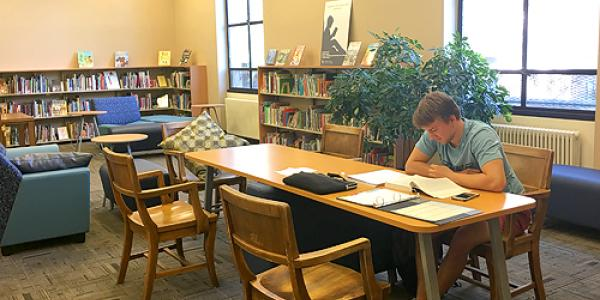 A student works at a table near the C&YA Collection