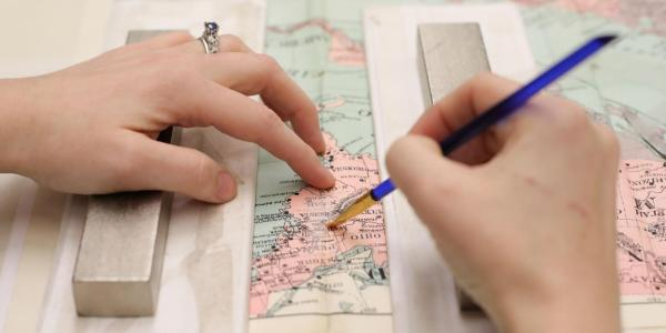 Conservator mending tears on a map