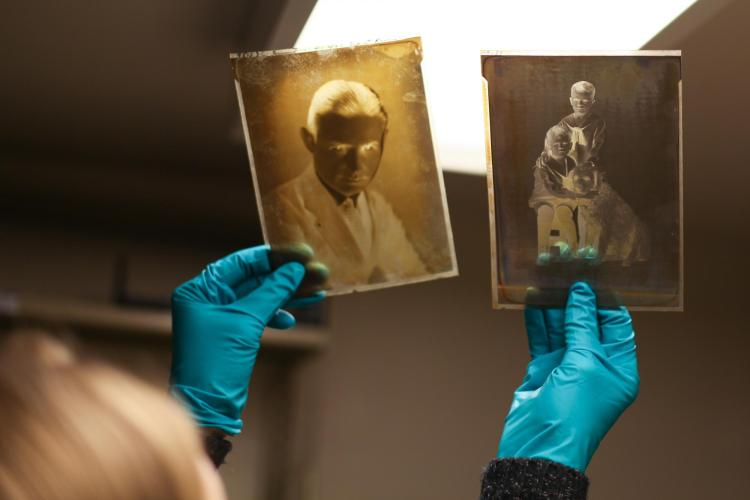 With blue gloves, the photo archivist holds up two old negatives to a light.