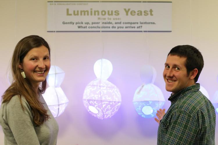 ATLAS graduate student, Lila Finch, conceptualizing data from Zach Wilson, a doctoral student in Molecular, Cellular, and Developmental Biology, in front of their data visualization, Luminous Yeast.