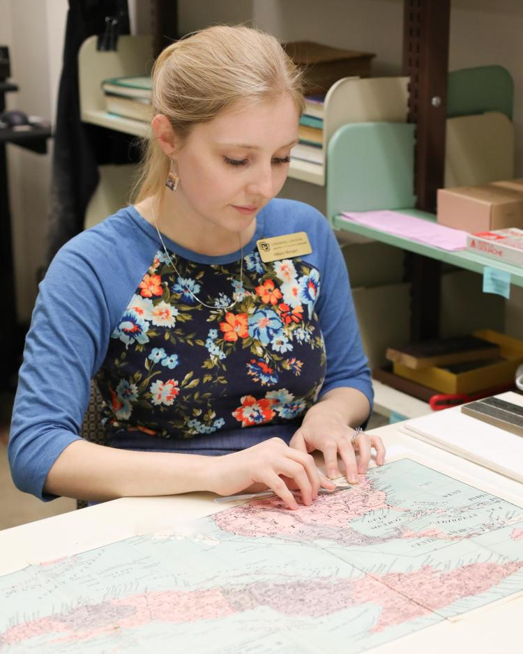 Hillary Morgan from CU Boulder Preservation, repairs a torn map.