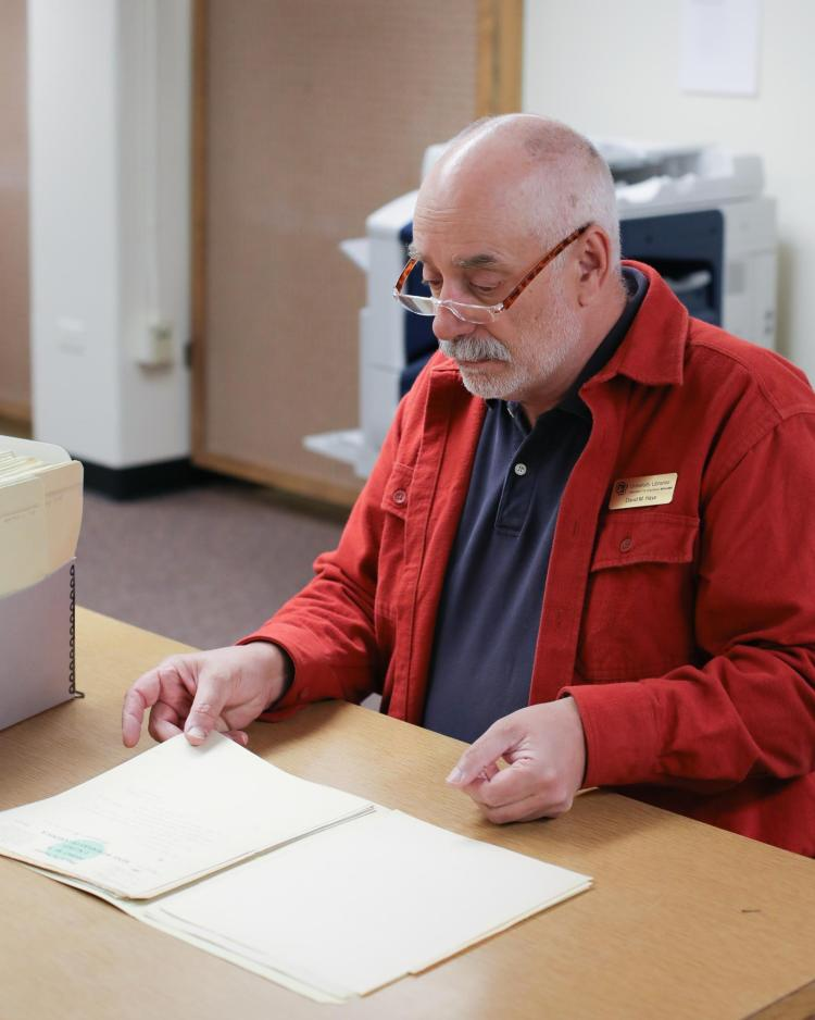 Archivist David Hays examining personal letters in an archive collection.