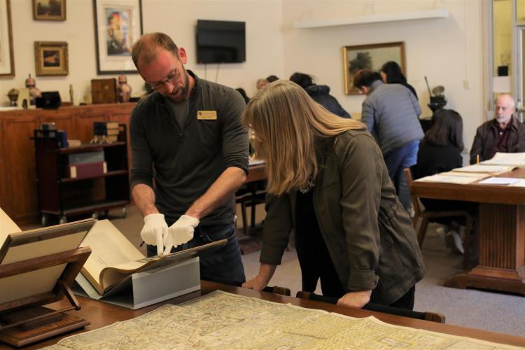 University Libraries' Adam Lisbon and Susan Leigh Guinn-Chipmann look at rare items from the Asian Studies collection.
