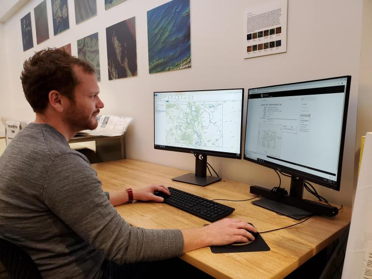 Philip White uses two screens to explore the GeoLibrary.