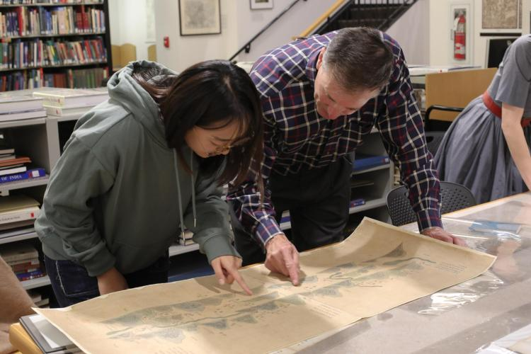 Wesley Brown looking at a map with a student.