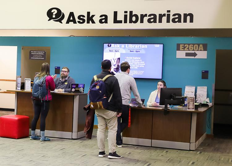 Students ask for help at Ask A Librarian desk.