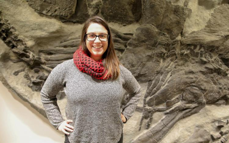 Adrienne Strock in front of large fossil.