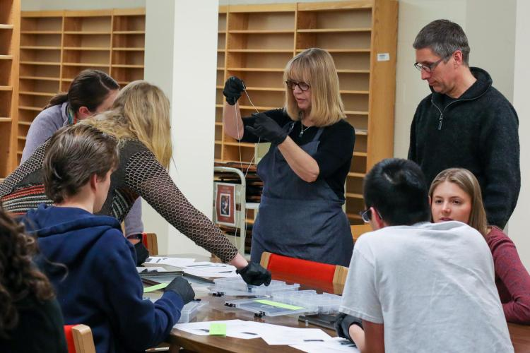 Guinn-Chipman works on bookbinding with students.