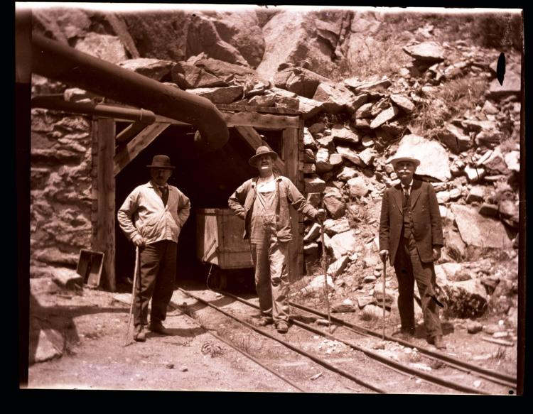 Three men standing outside a mine shaft, unknown date