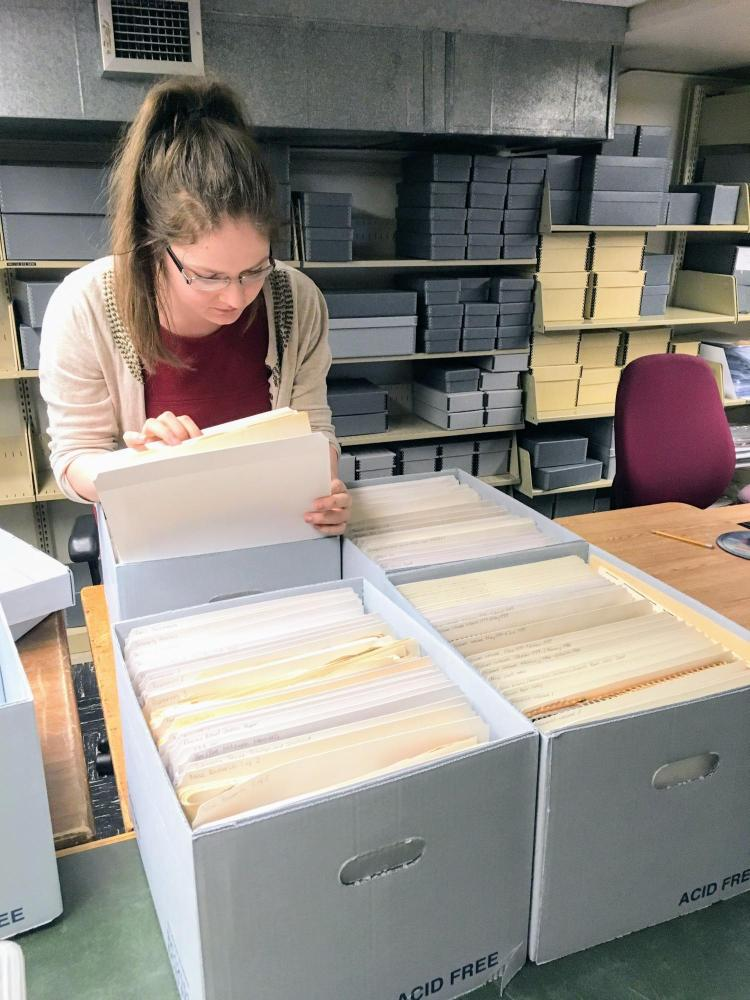 A student working in the Libraries' Archives, sorting papers.