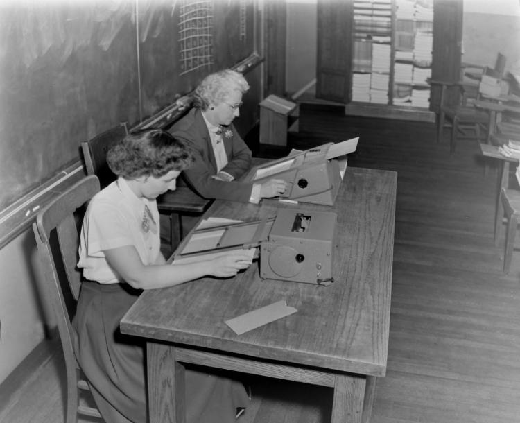 Two women reading using a metronoscope to help focus their reading in the 1950s.