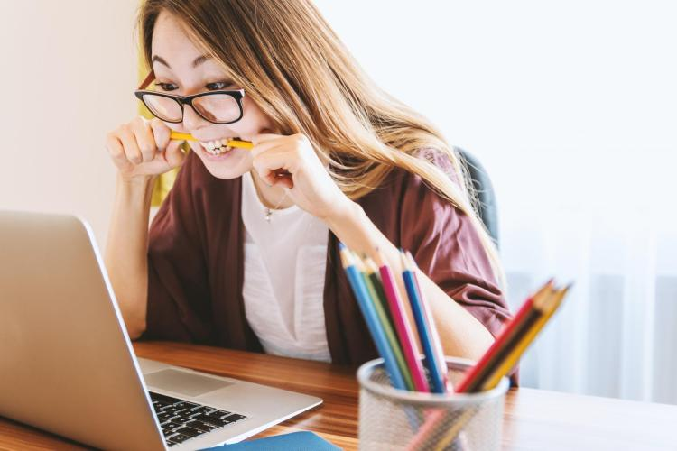 Student biting pencil in front of laptop