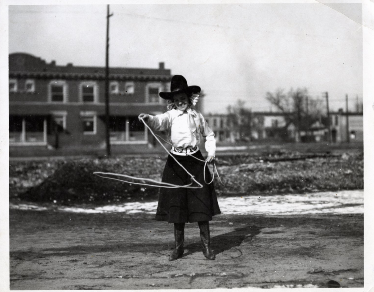"Rodeo performer Mayme Saunders Stroud spinning a small rope, in a trick called the ""flat rope,"" Rocky Ford, Colorado, 1918"