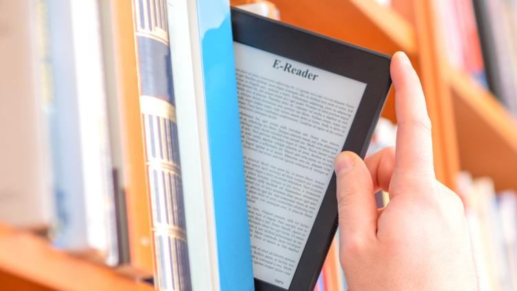 Person pulling e-reader from bookshelf