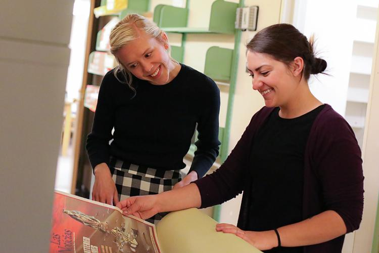 Project Archivists Jane Thaler and Katelyn Morken examine oversized pieces of the archives.