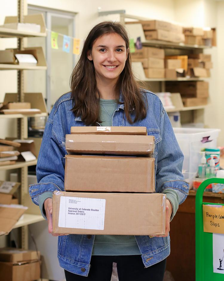 Female student carries a pile of boxes being mailed to users with library materials.